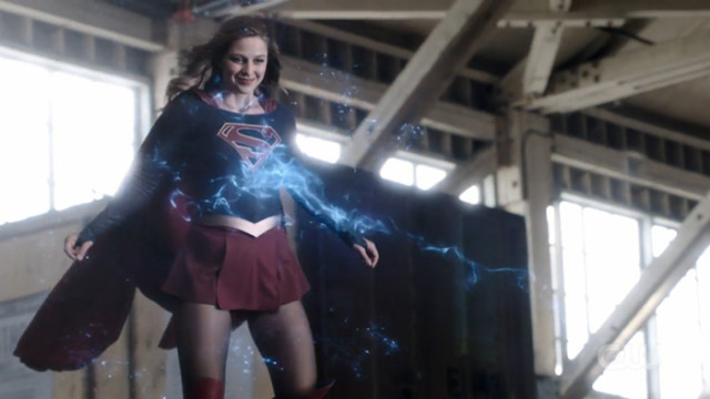 Kara flying and smiling while being hit by laser beams.