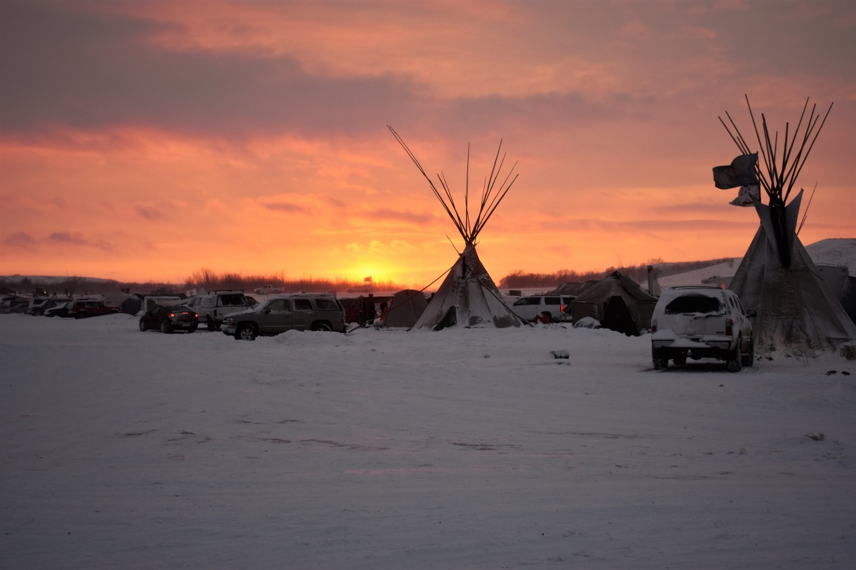 Cars and teepees in front of a sunset. Oceti Sakowin encampment, December 5, 2016. Photo by Jen Deerinwater. Read more coverage about DAPL resistance here.