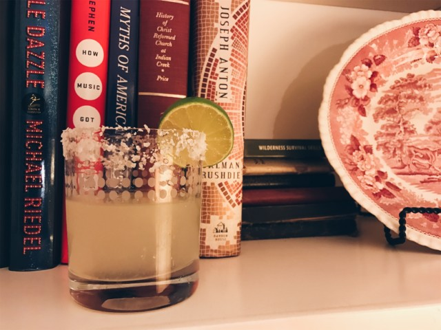 photo of completed cocktail in front of my mother's book collection and decorative plate