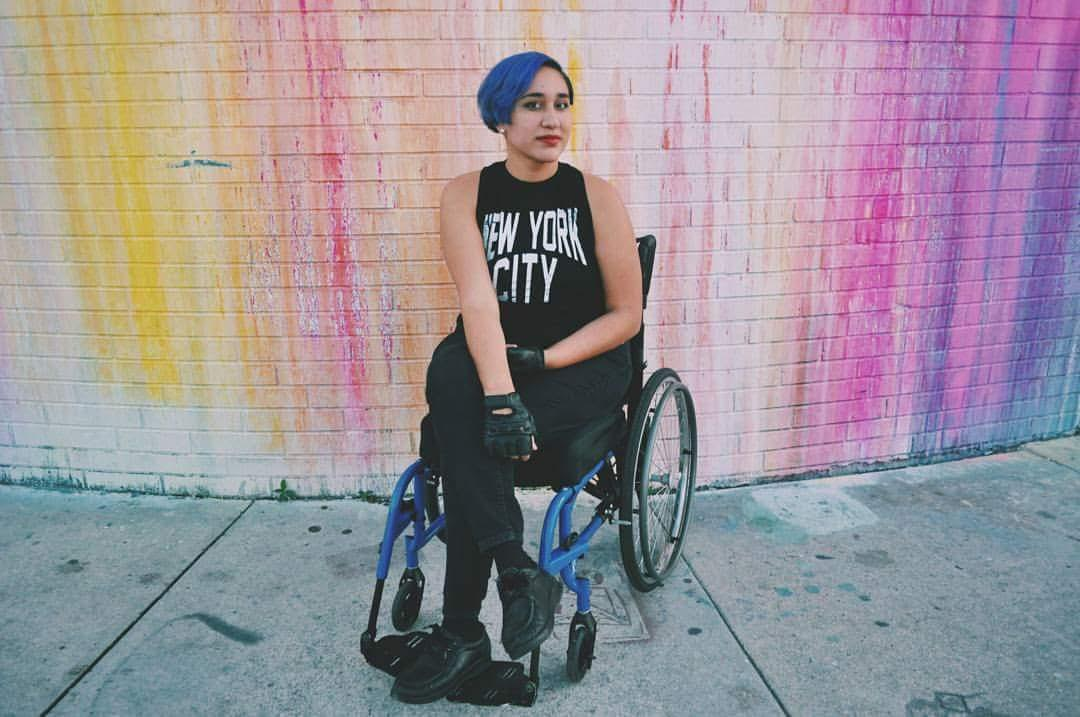 Annie, a young Latinx woman with blue hair in this photo, sits in her wheelchair with legs crossed. She is in front of a white wall that's been splashed with yellow, pink, and purple paint, and is wearing black head-to-toe, with a shirt that says New York City in white block letters.