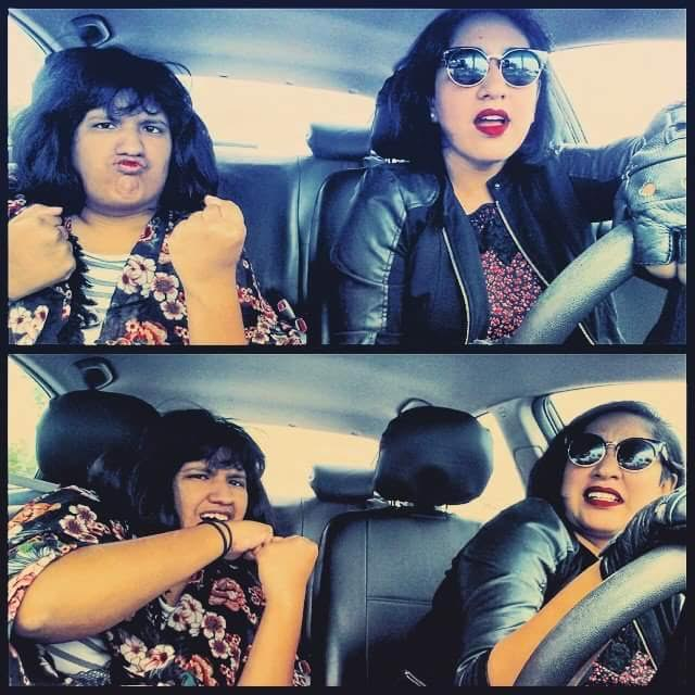 Annie, a young Latinx woman with black hair and red lips in this photo, sits in the driver's seat of a car next to her sister Emily, a young Latinx woman with black hair. In the top photo, Emily raises her fists in a fighting pose; in the bottom, they both playfully appear as if the car has taken a sharp turn.