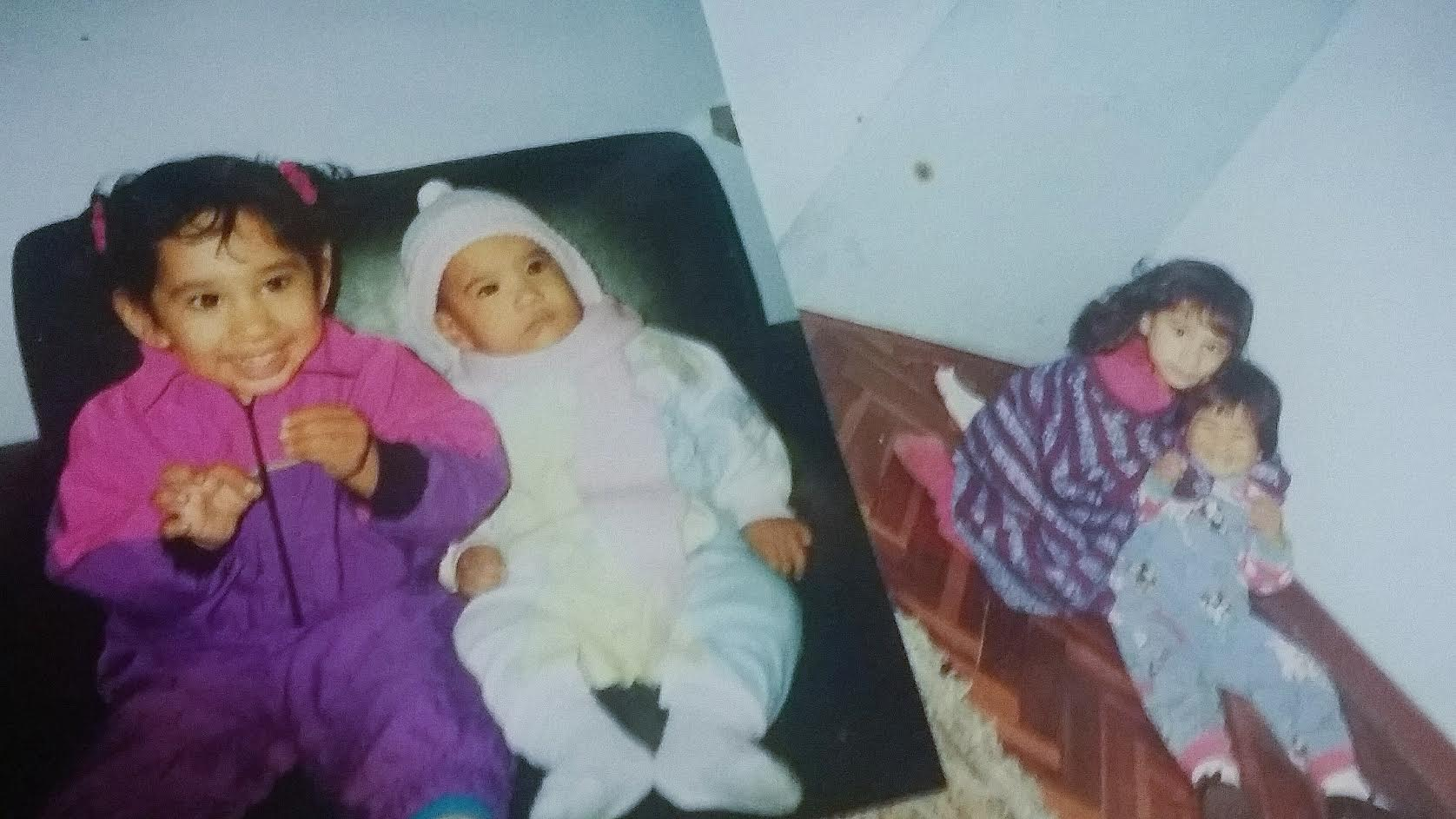 Two photos side by side. On the left, sisters Emily and Annie are very young. Emily is in a white onesie and Annie is in a pink and purple jumpsuit. In the right-hand photo, both siblings are slightly older but still children, with Annie putting her arms around Emily to hug her from behind. Annie wears purple and pink, Emily is in blue denim overalls.