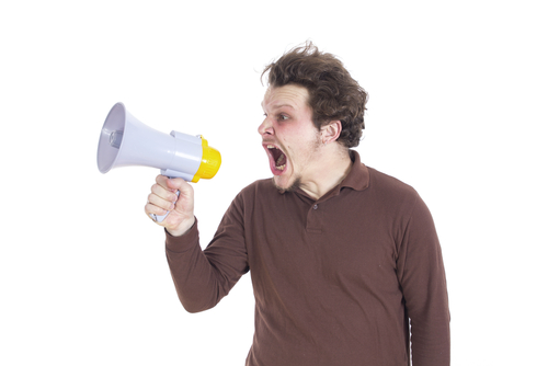 white man shouting into megaphone