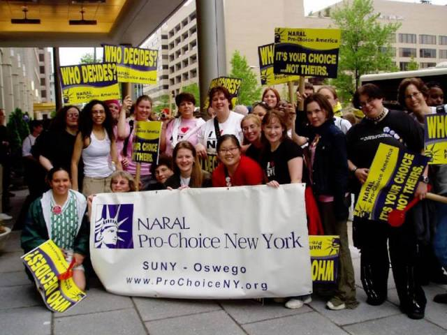 personal photo of the author with a group of 20 other activists from SUNY Oswego at the March for Women's Lives standing behind a NARAL Pro-Choice banner