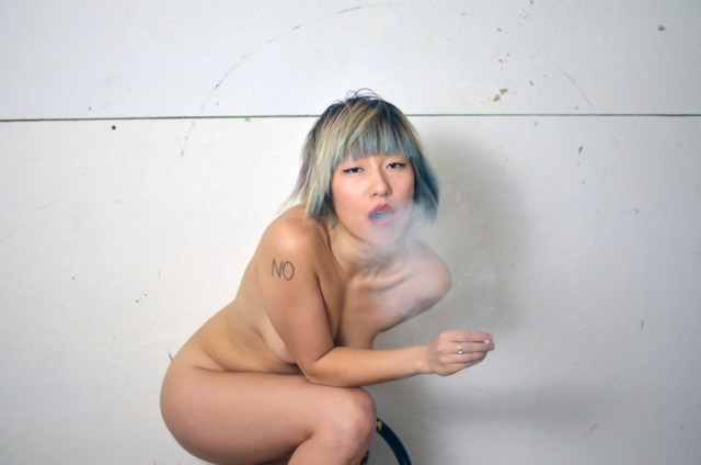 styrxfoam sitting naked on a stool against a white wall, exhaling smoke
