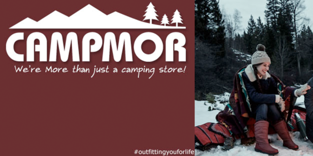 "Campmor logo, featuring the tagline ""We're more than just a camping store!"" and an image of a brown-haired young white woman, sitting at a snowy campsite, smiling and looking downward."