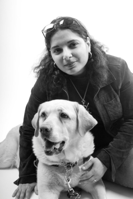 An Arab-American woman with dark hair, a black jacket, and sunglasses perched on her forehead looks into the camera. She is sitting with her arm around a large dog with light-colored fur. The photo is black and white.
