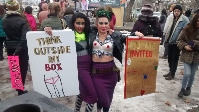 """Two people pose for a photo while holding protest signs; one reads """"think outside my box"""" and the other is an invite to a counter-protest dance party"""