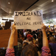 "A woman holds up a black and white sign in a large crowd at an airport protest that reads ""Immigrants are welcome here."""