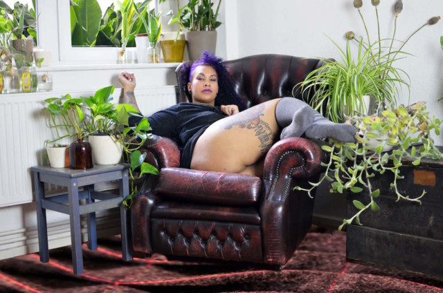 Valentine, in a soft shirt and tall socks and no pants, lounging in a tuffed leather chair in a bright, plant-filled room