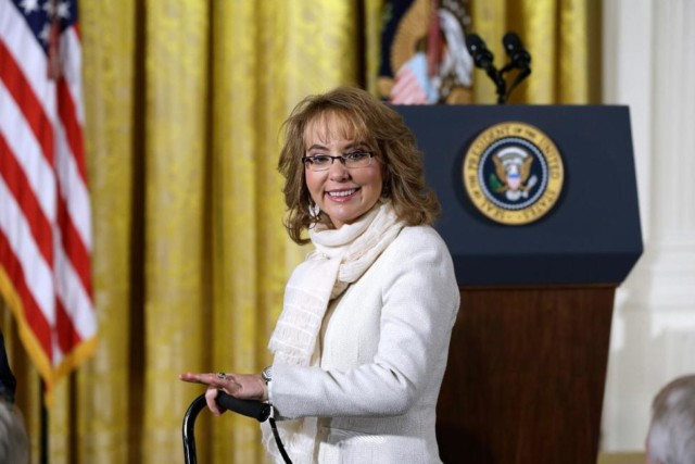 A white woman with shoulder-length dirty blonde hair and black glasses stands in front of a podium with a United States seal on it and an American flag to the left. She is wearing a white jacket and leaning on a cane that shows up in the bottom of the frame.