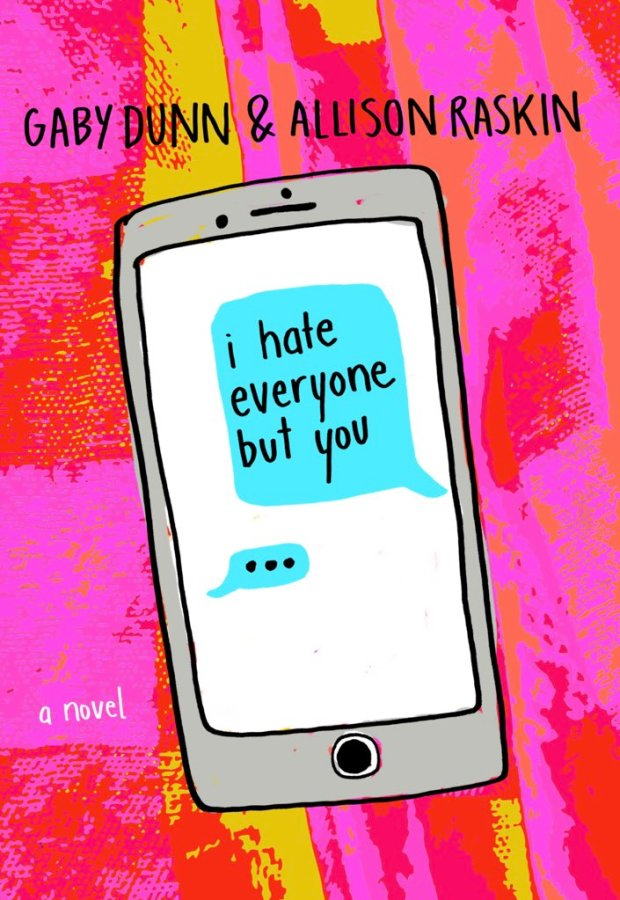 The cover for I Hate Everyone But You, with a smartphone showing a text message containing the title is imposed on a hot pink and red background.