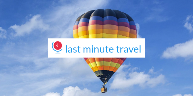 last minute travel logo set over an image of a brightly-colored hot-air balloon against a blue sky with clouds