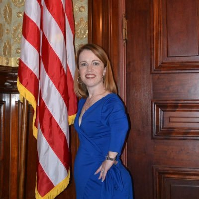 A white woman with long red hair and red lips stands next to an American flag in a room with a dark wooden door. She is wearing a blue dress and has her hand on her hip.
