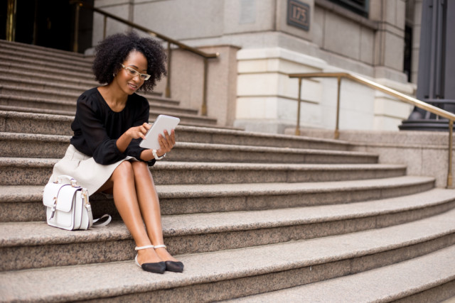 A woman reading on some stone steps