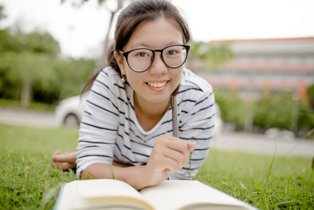 girl with oversized glasses reading a book outside on the grass