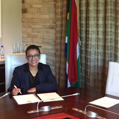 A woman with closely shaved black hair and black rimmed glasses sits behind a desk in a government office smiling at the camera. There is a South African flag in the background and various papers are on the desk. She is wearing a navy blue blazer and black shirt.