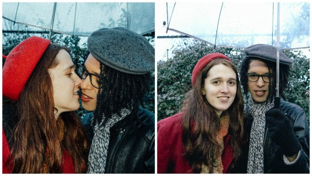 Two photos side by side: on the left, a white woman in her twenties with long brown hair and wearing a red coat and beret and a black woman in a black leather jacket with a gray scarf and beret lean toward each other in a kiss. On the right, the two of them face the camera, smiling. They are under an umbrella in both photos.