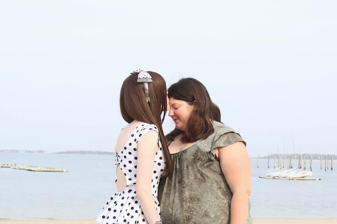 Two people stand on the shore against the background of the sea. They both have brown hair and are wearing dresses; the person on the left is in a white dress, and the person on the right is in green. The person on the left is leaning in to kiss the other one's forehead.