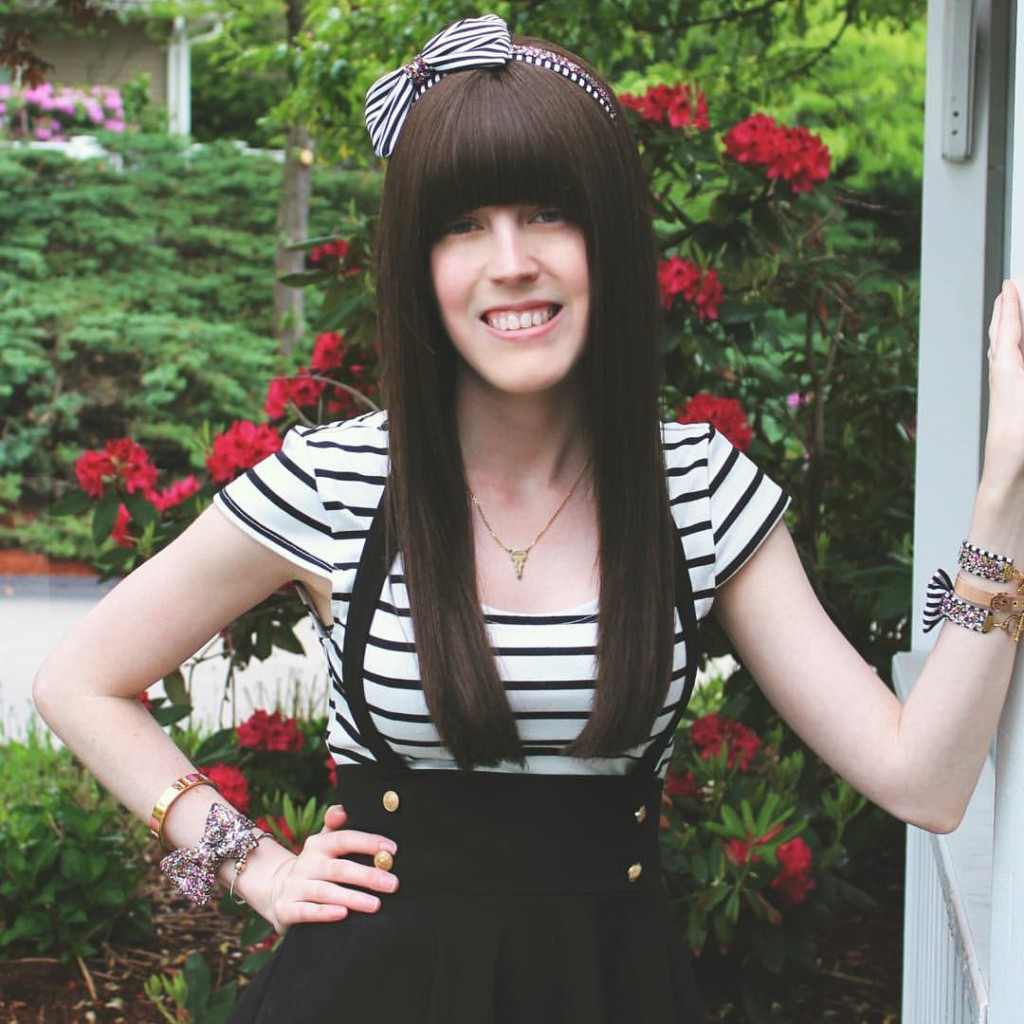 A white nonbinary person with long brown hair and blunt bangs stands against a backdrop of a hedge with red flowers on it. She is wearing a black and white striped dress and has her hand on her hip.