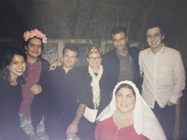 A group of seven people, six standing in a back row and one crouching down in front, smile into the camera. Some of them are wearing parts of Halloween costumes, including a veil, a gold crown, and a crown of flowers.