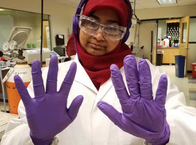 A person in a hijab and lab coat with purple gloves and safety goggles.