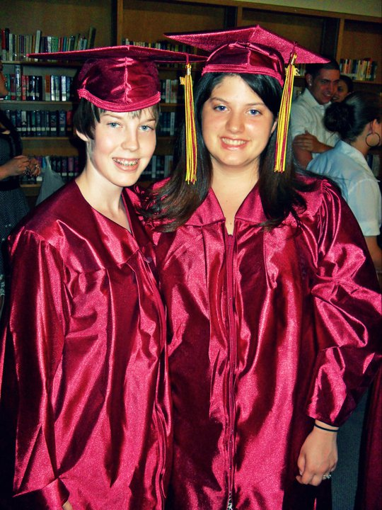Two people smile into the camera wearing burgundy graduation caps and gowns with gold tassels.