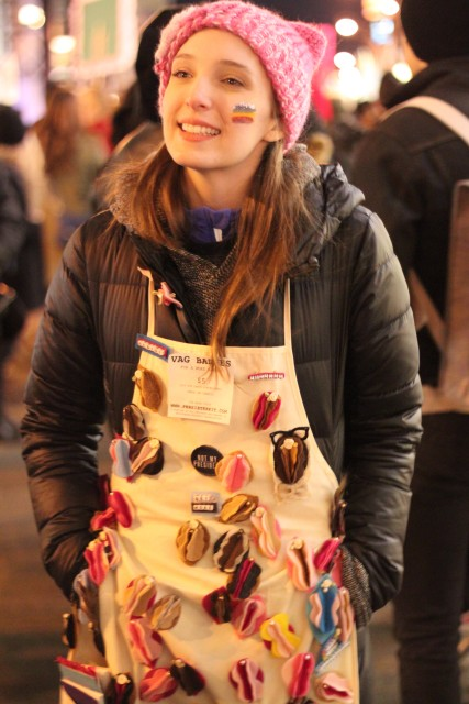 """A person wearing a pink """"pussy hat"""" and an apron with lots of buttons and sculpted vulvas pinned to it"""
