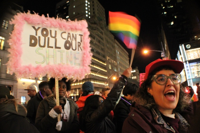 A group of protesters, one waving a rainbow flag, one holding a sign that reads YOU CAN'T DULL OUR SHINE, and one person shouting or chanting