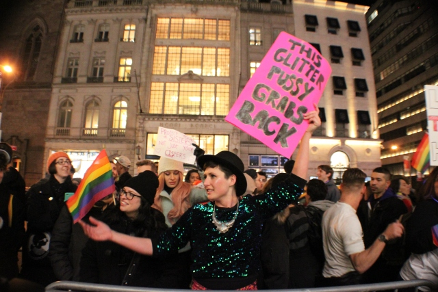 A group of protesters, with one person in the foreground wearing a glitter shirt and holding a sign that reads THIS GLITTER PUSSY GRABS BACK
