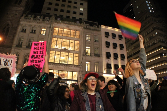 A group of protesters in motion, waving a rainbox flag and a sign that reads WE'RE HERE WE'RE QUEER WE'RE NOT GOING ANYWHERE