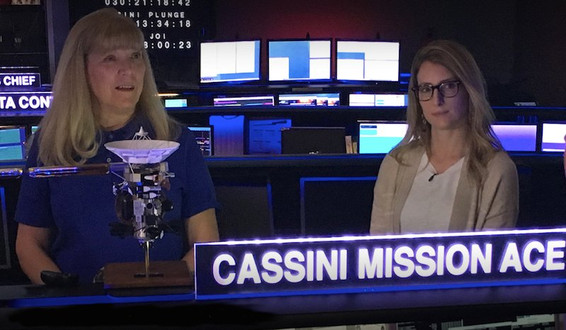 """Two white women stand next to each other in a mission control room, with the text """"Cassini Mission Ace"""" lit up in front of them. Linda Spilker is blonde and wears a blue polo shirt; Molly Bittner has glasses and a tan cardigan. There are numerous monitors lit up behind them."""