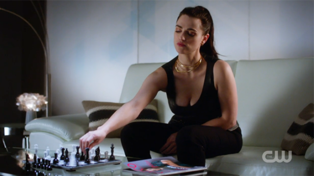 Lena reaches for a chess piece