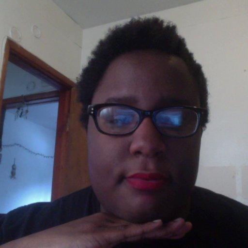 A black woman with short curly hair, red lipstick, and thick black glasses looks into the camera with an open doorway in the background