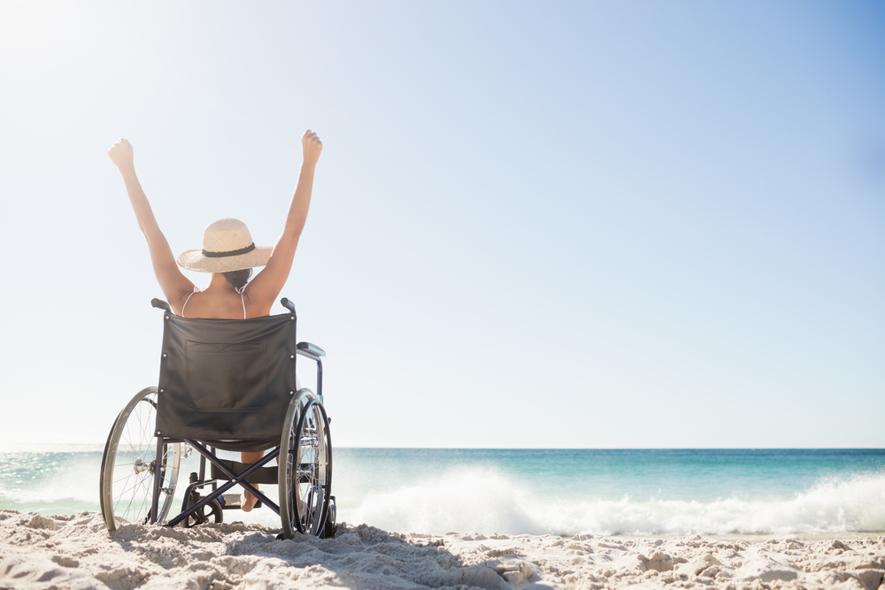 View from behind of a woman raising her arms over her head while sitting in a manual wheelchair on the beach. She is wearing a straw hat with a wide brim, and you can see the ocean in the background.