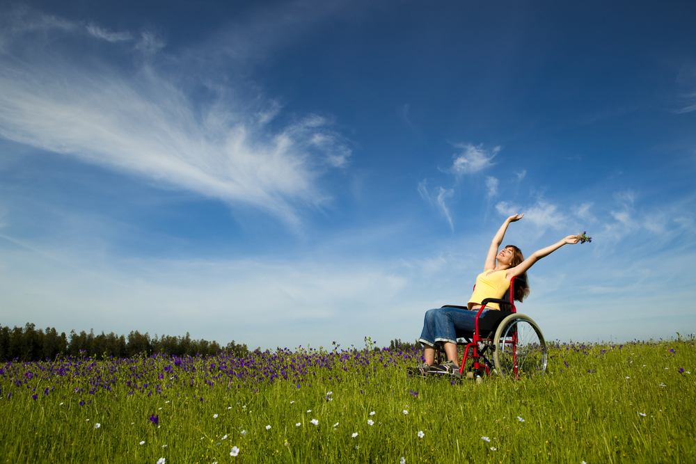 A woman in blue jean capris and a yellow sleeveless top raises her arms over her head while sitting in a red manual wheelchair in the middle of a meadow.