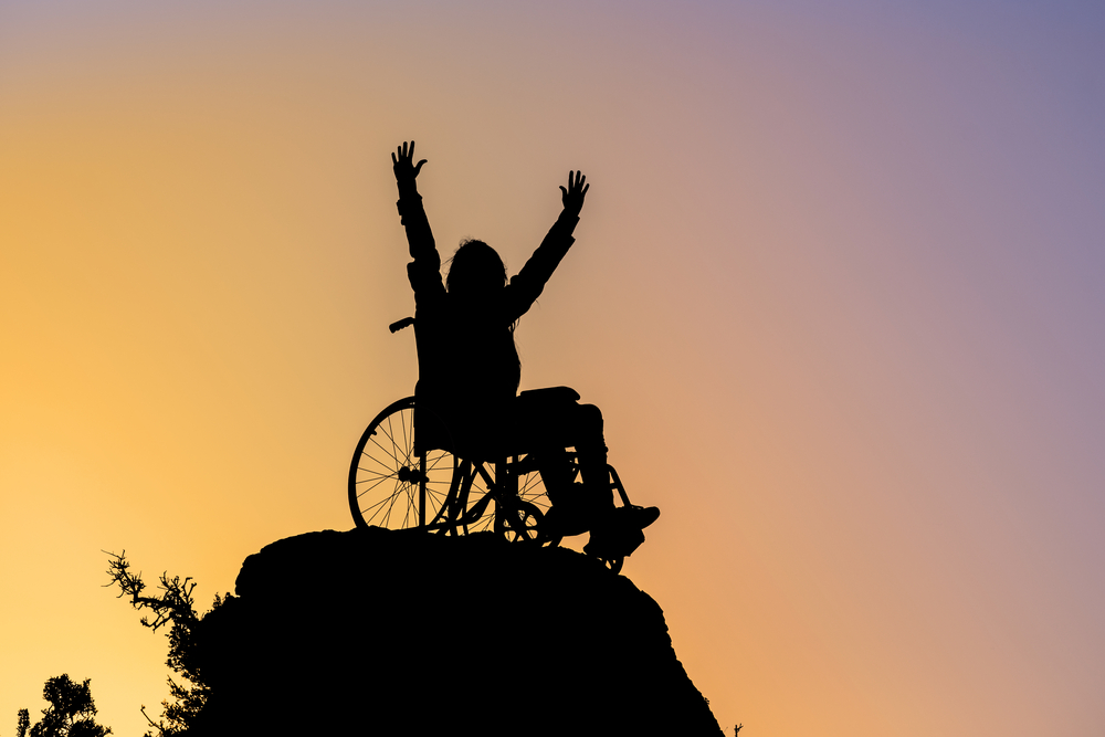 In silhouette against a sunset background, a person in a manual wheelchair raises their arms above their head on a mountaintop.