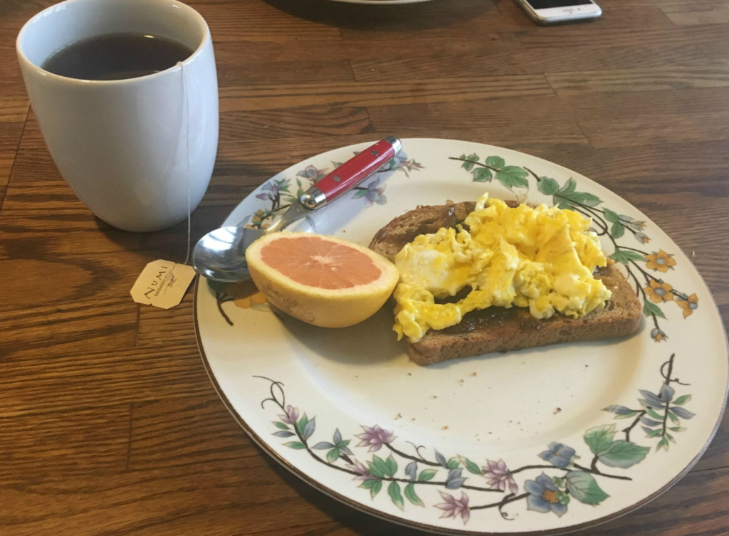 A plate of food showing eggs on toast with a small grapefruit slice next to it. There is a white mug full of tea in the background.