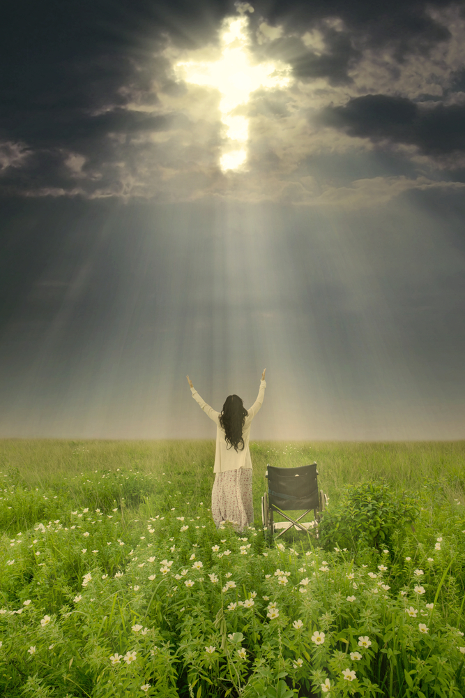 Rear view of a woman in a long white skirt and top standing in a meadow next to an empty manual wheelchair, with her arms raised toward a dark sky. A cross can be seen through the clouds and is bathing her in a beam of light.