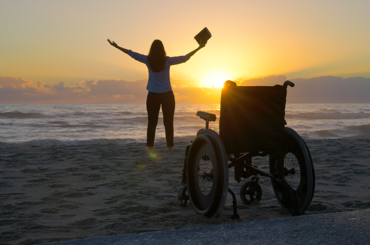 In silhouette against a sunset background, a woman raises her arms towards the sky and holds a book in one hand. A manual wheelchair sits unoccupied toward the back of the frame.