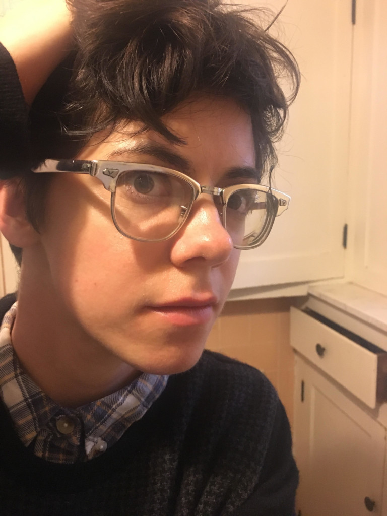 A white woman with short brown hair and glasses fixes her hair by running her fingers through it. She is wearing a blue and white plaid shirt underneath a black houndstooth sweater.