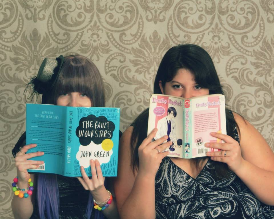 Two people jokingly hide their faces behind book covers. The person on the left has long brown hair cut into severe bangs and is wearing a small hat tilted off the right side of their head. They're behind the book cover of The Fault in Our Stars. The one on the right has darker, longer hair and is wearing a black and white top. They're behind the cover of a book in the Fruits Basket anime series.