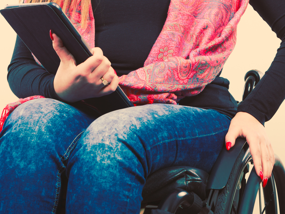 A woman sits in a manual wheelchair holding a tablet computer. She is wearing blue jeans and a pink scarf and has long red nails. The photo only shows her from the neck down, no head.