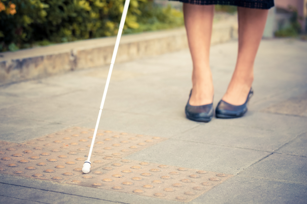 A woman's feet walking along a sidewalk. She has a white cane out in front of her. You can only see her black shoes, part of her calves, and the tip of the cane.