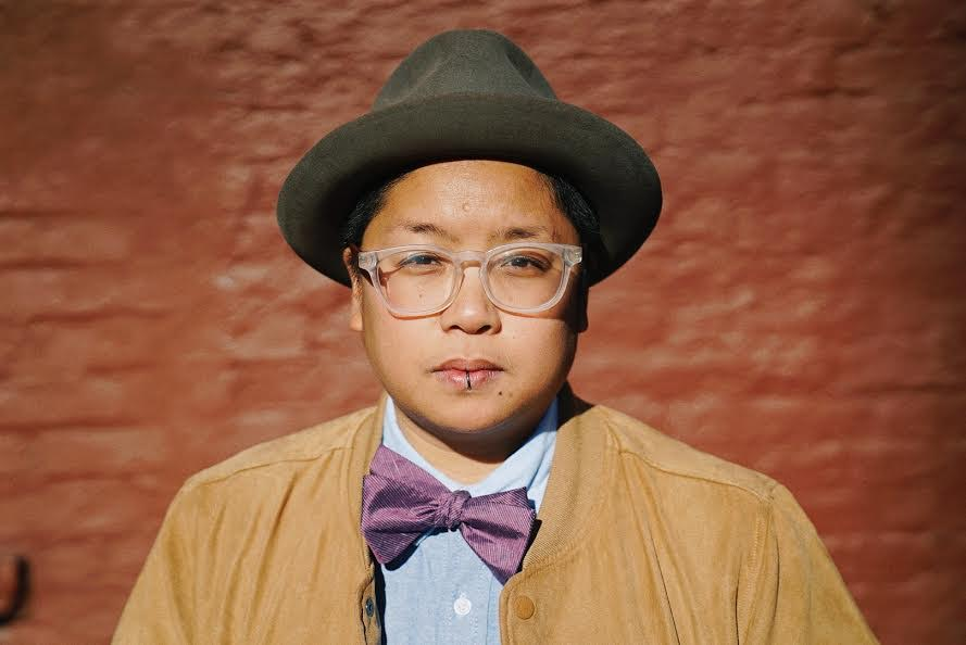 A Filipinx person looks into the camera against a brick wall background. They are wearing clear framed glasses, a grey bowler hat, a mustard yellow jacket and blue shirt, and a purple bow tie.