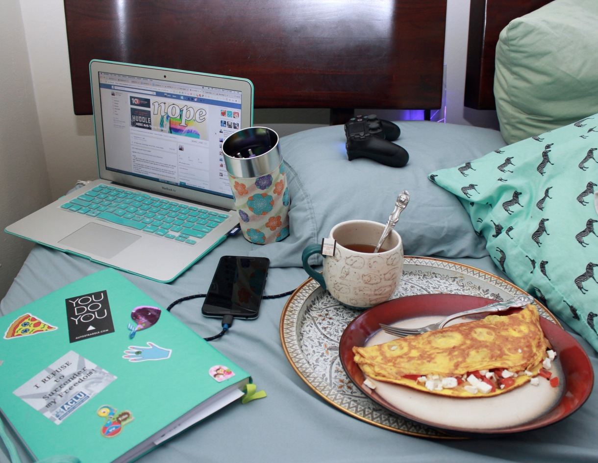Photo of a bed. There is a tray with tea and an omelette, a passion planner, colorful pens in a tea tin, a laptop, a Playstation controller, and a plugged in phone. Everything is teal.