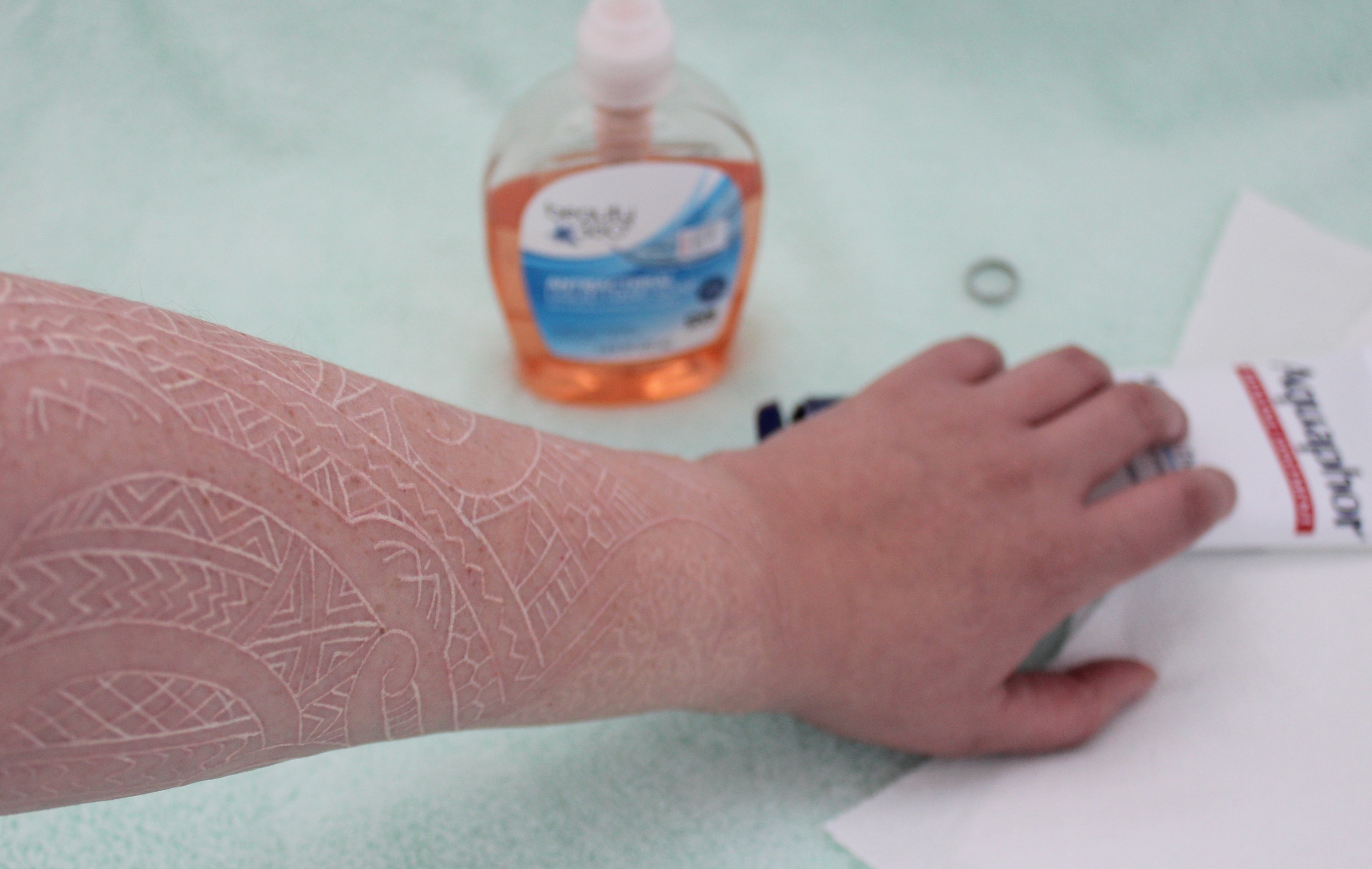 a tattooed arm reaching for aquaphor