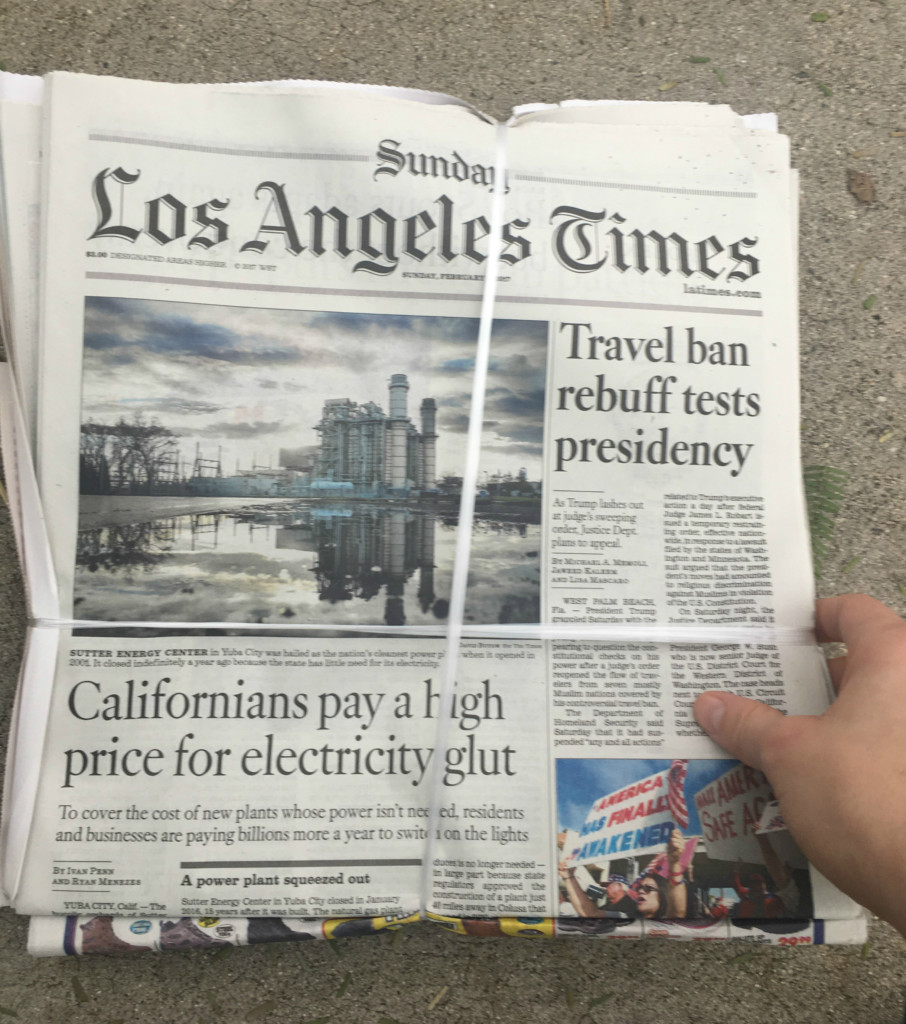 The front page of a Sunday edition of the Los Angeles Times, still wrapped in its packaging after being dropped off in the driveway.