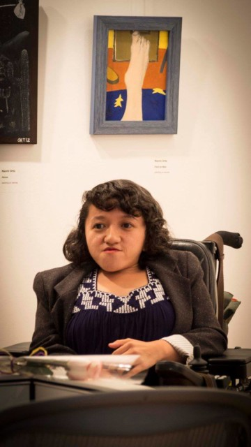 A young Asian woman with shoulder-length hair and wearing a black shirt with white trim sits in her wheelchair looking at the camera. There is a painting of a foot against a blue and orange background on the wall behind her.