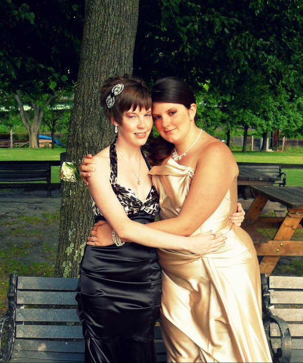 Two people hold each other around the waist in fancy prom dresses. The one on the left is in a black dress, while the person on the right is in gold.